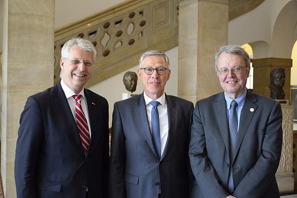 Drei Männer schauen in die Kamera; im Hintergrund das Treppenhaus des Bremer Rathaus