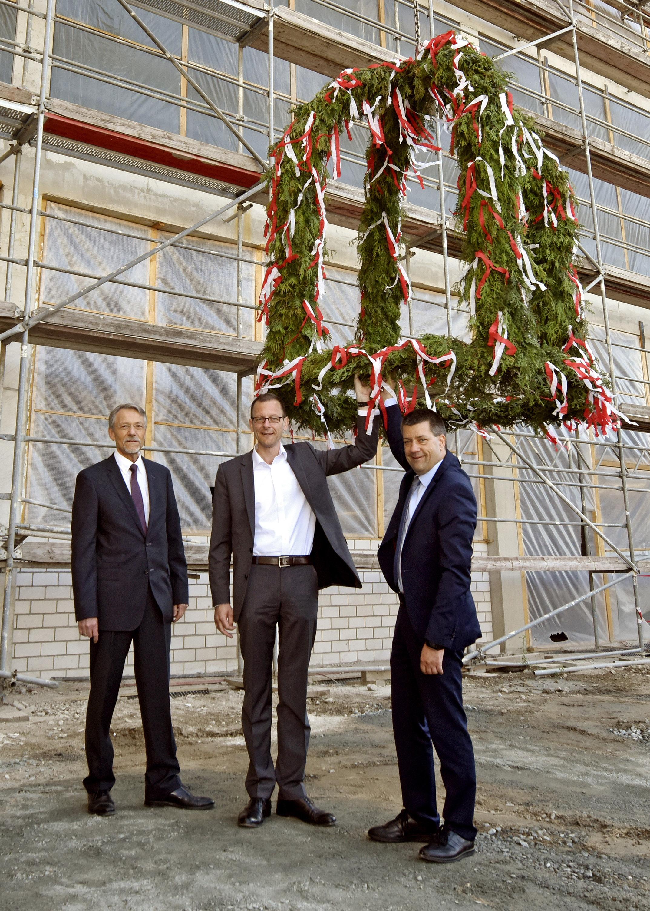 Drei Männer neben einem Richtkranz, der gehisst wird