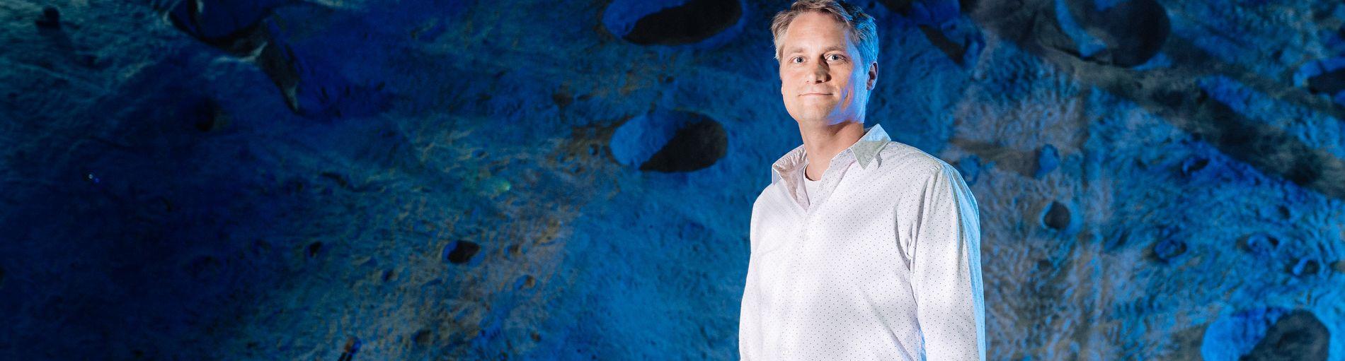 Dr. Sebastian Bartsch vor einem mondähnlichen Hintergrund