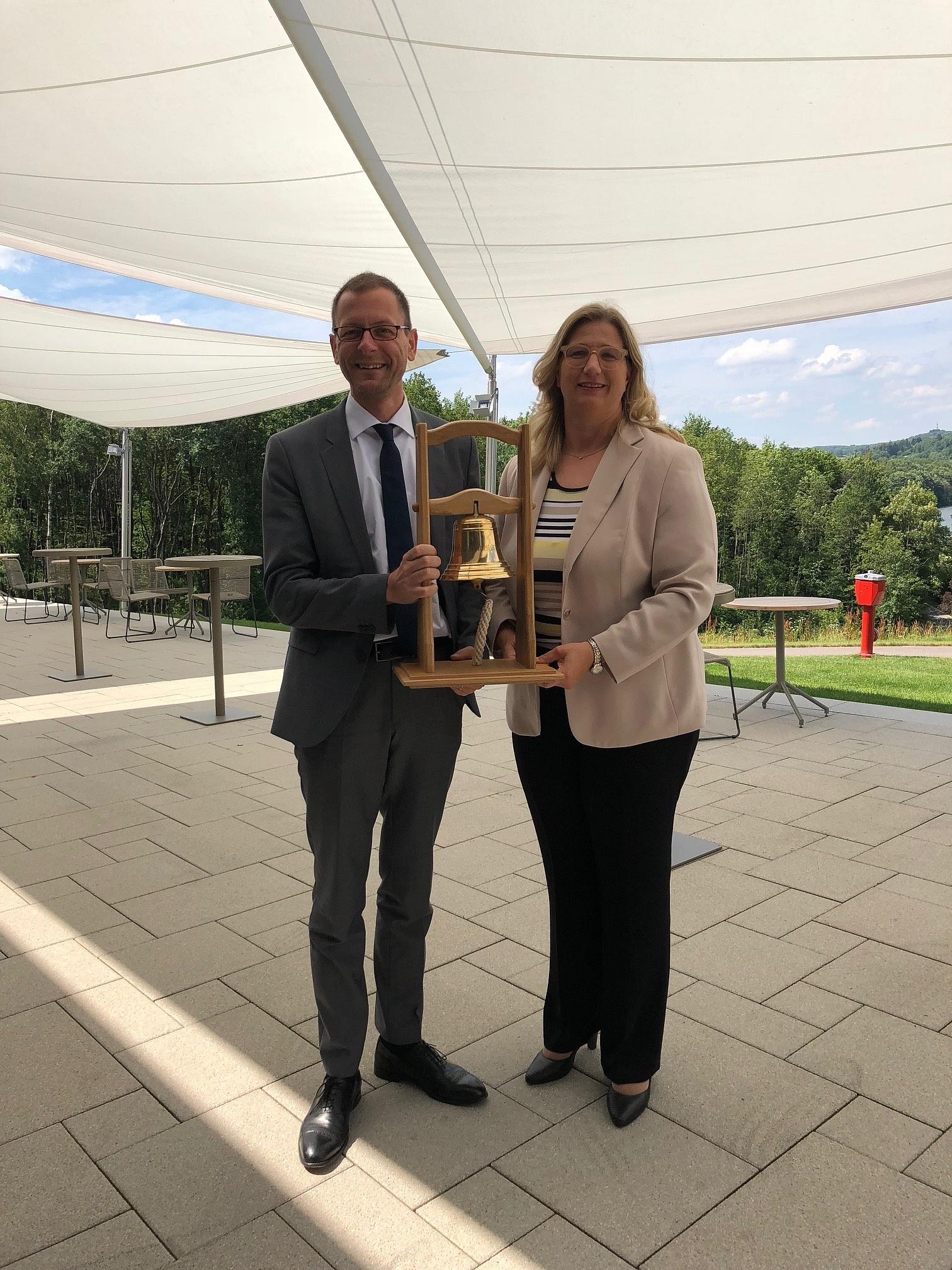 Anke Rehlinger übergibt Senator Martin Günthner eine Glocke