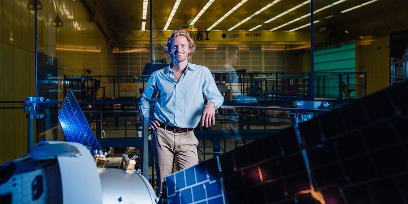Daniel Pika neben einem Satelliten in einer Halle