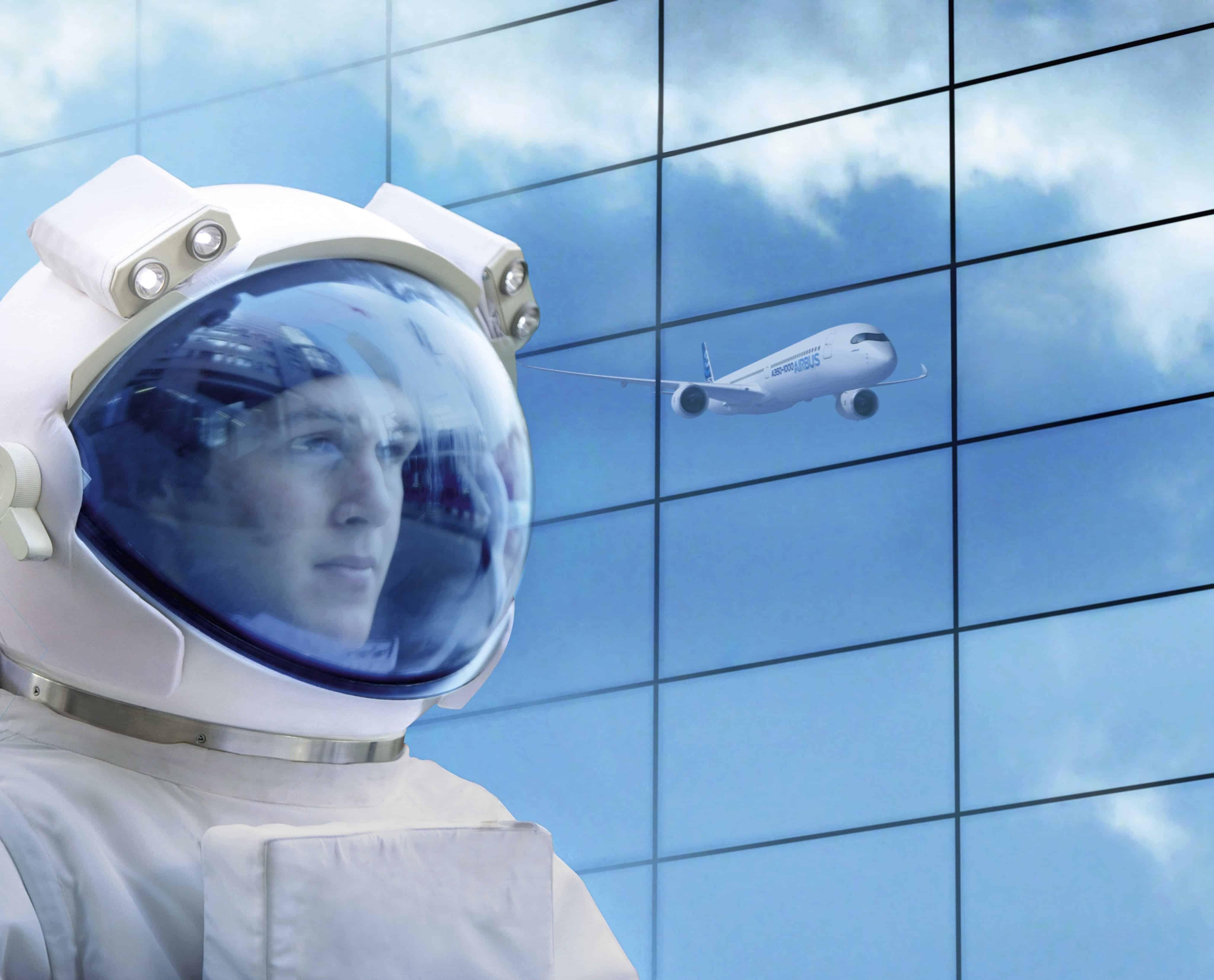 Eine Person in Astronautenkleidung vor einer Glaswand in der sich ein Flugzeug spiegelt