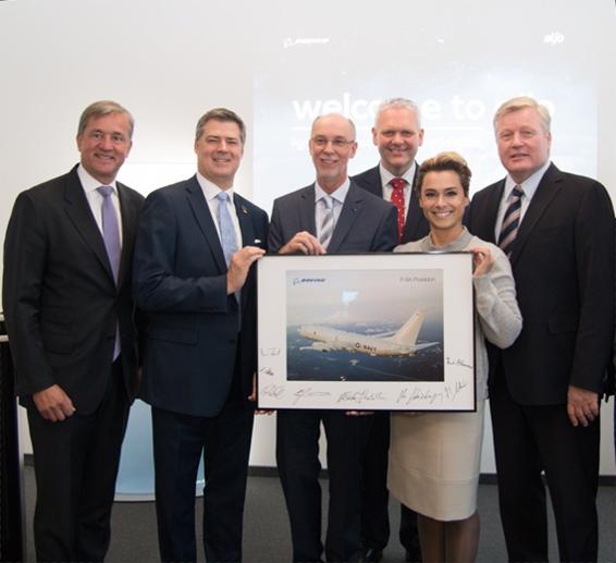 Sechs Personen stehen zusammen; sie halten ein Bild mit einem Flugzeug in den Händen