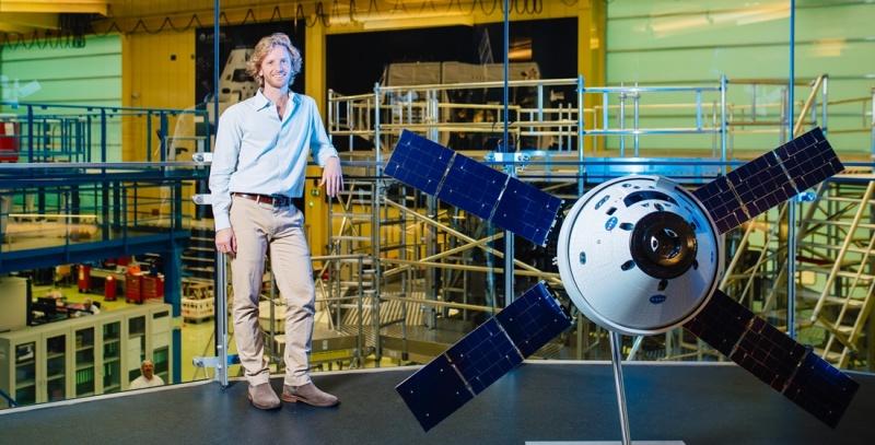 Ein Mann in einer Werkshalle steht neben einem Satelliten