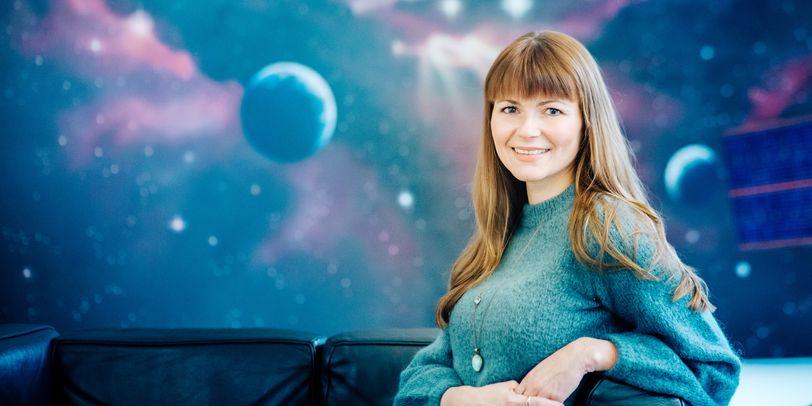 Eine sitzende Frau blickt in die Kamera; im Hintergrund ein Bild des Weltalls mit einigen Planeten