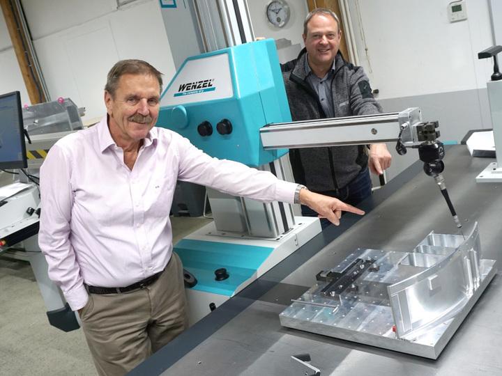 Zwei Männer präsentieren eine 3D-Messmaschine