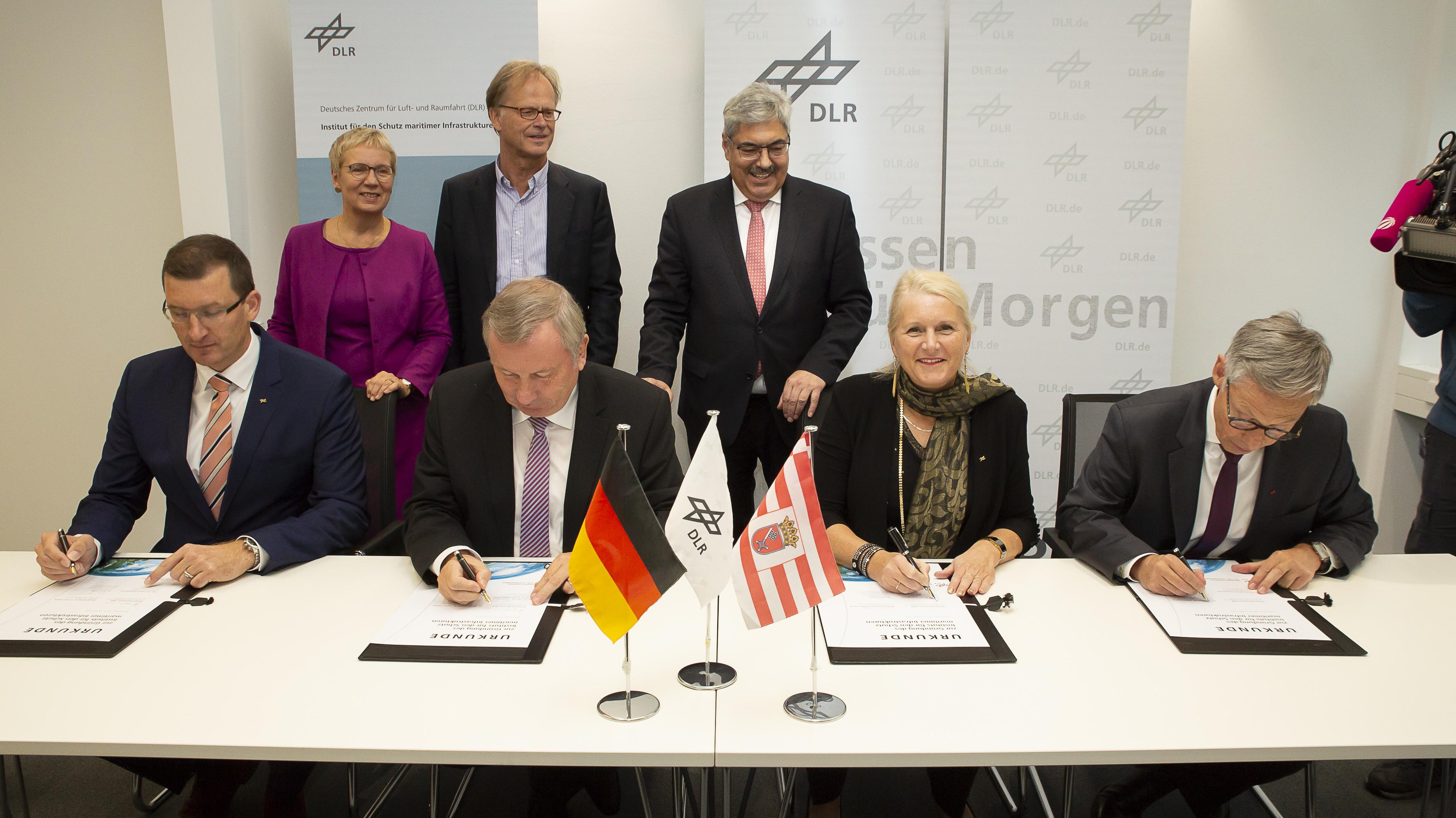 Vier Personen beim unterzeichnen von Unterlagen; dahinter stehen drei weitere Personen