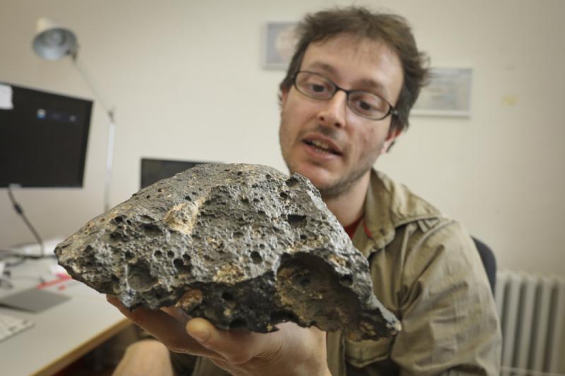 Ein Mann zeigt eine große Gesteinsprobe