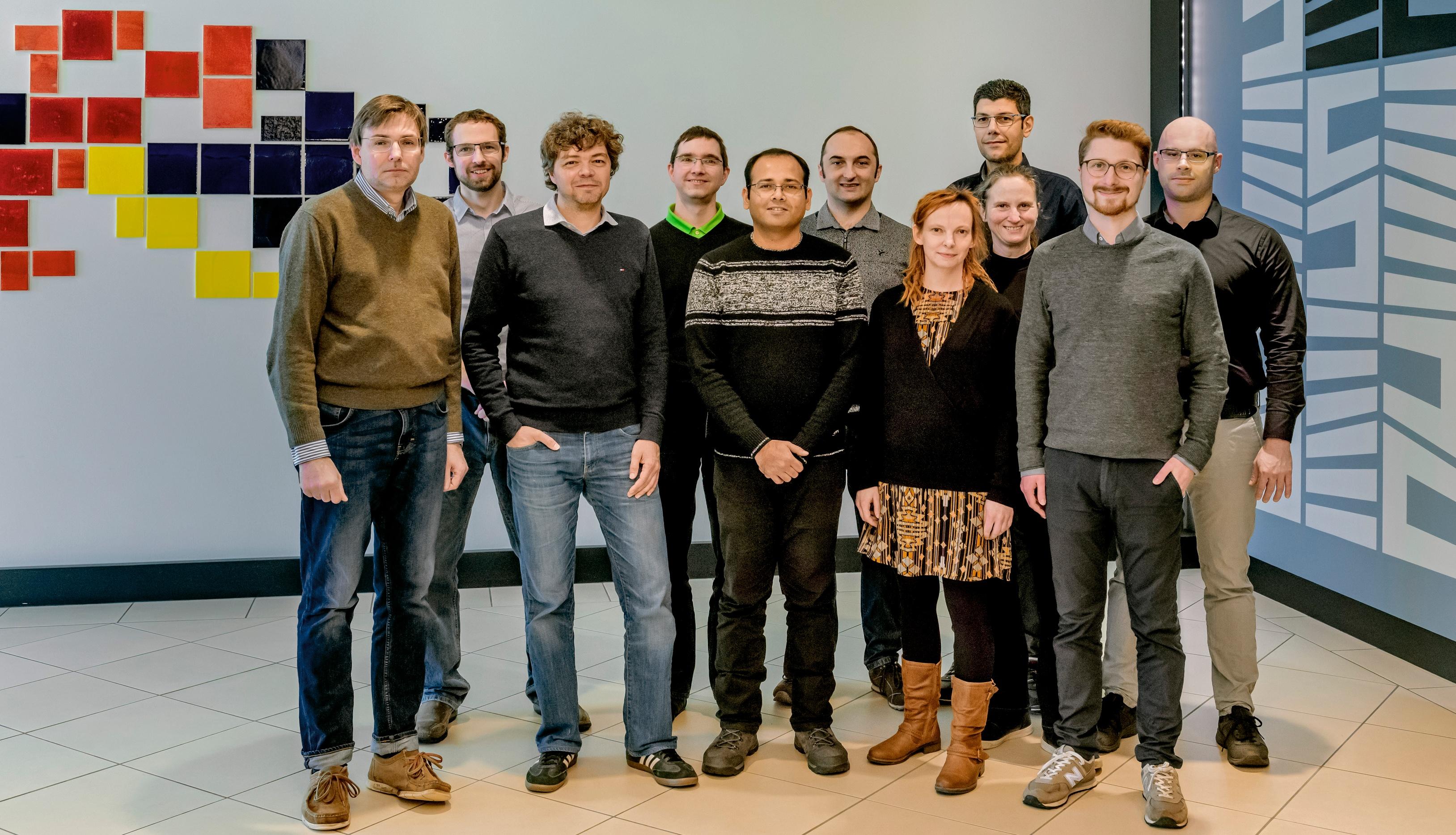Gruppe von elf Personen, die in die Kamera schauen