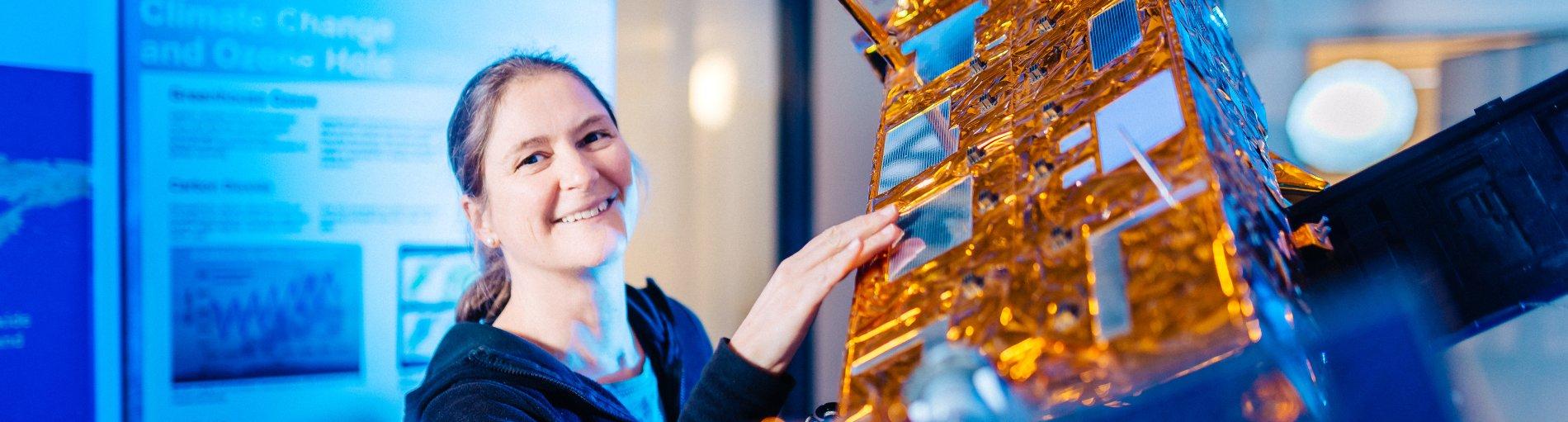 Eine Frau neben einem Model eines Satelliten