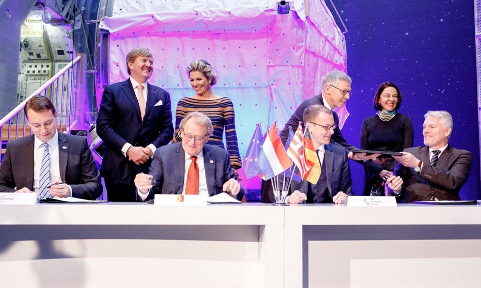 Einige Personen bei einer Vertragsunterzeichnung; im Hintergrund befinden sich Elemente der Raumfahrt