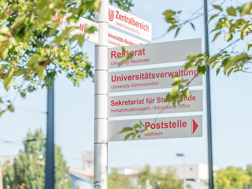 Ein Pfahl mit einigen Hinweisschildern im Bereich der Uni Bremen