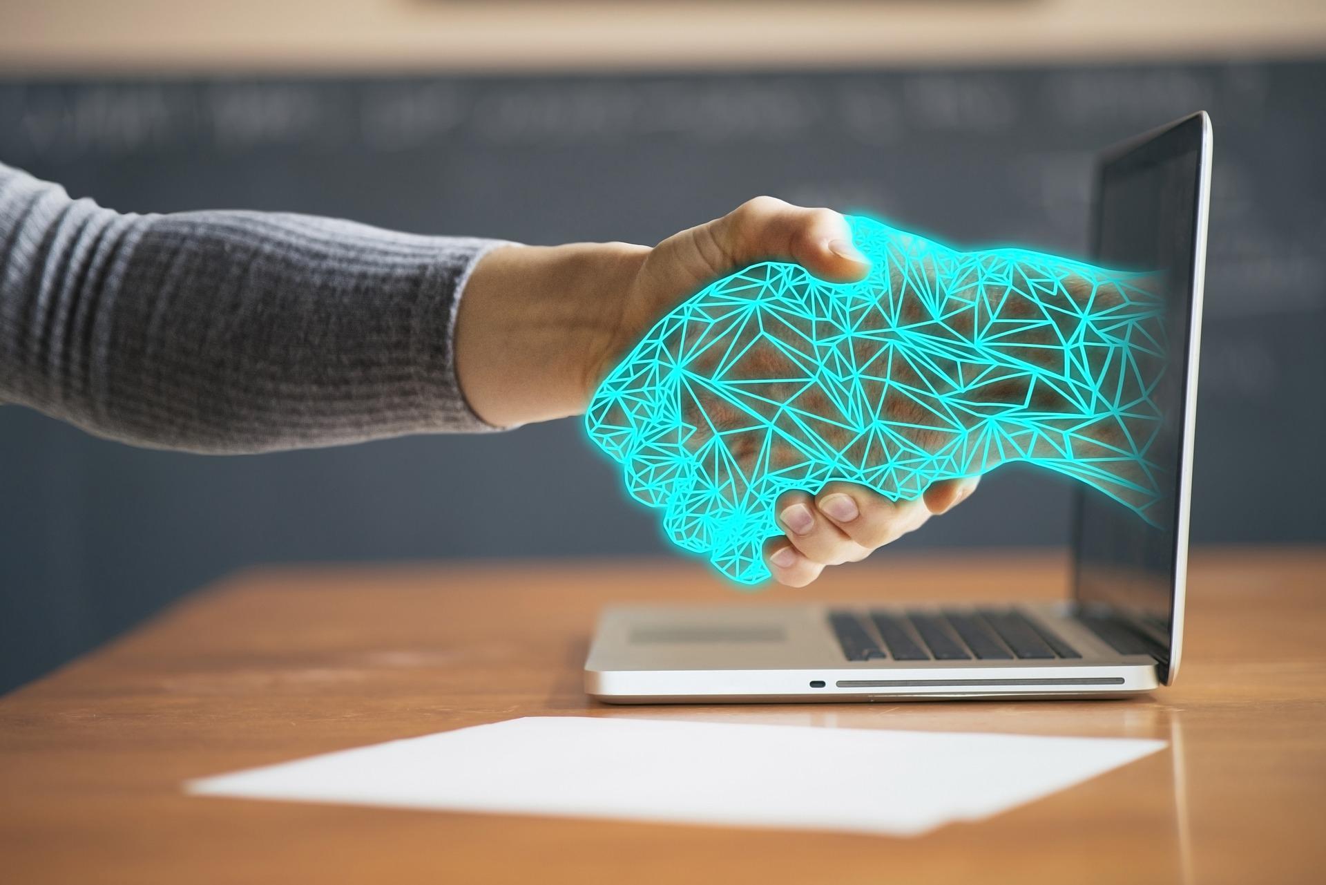 Zwei Hände, die einander reichen. Dabei kommt eine Hand aus dem Laptop und ist aus künstlicher Intelligenz geformt