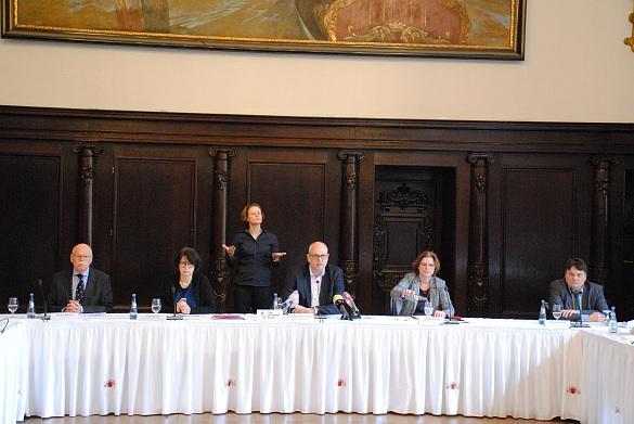 Fünf Senator:innen im Rathaus bei einer Pressekonferenz; im Hintergrund eine Gebärdende