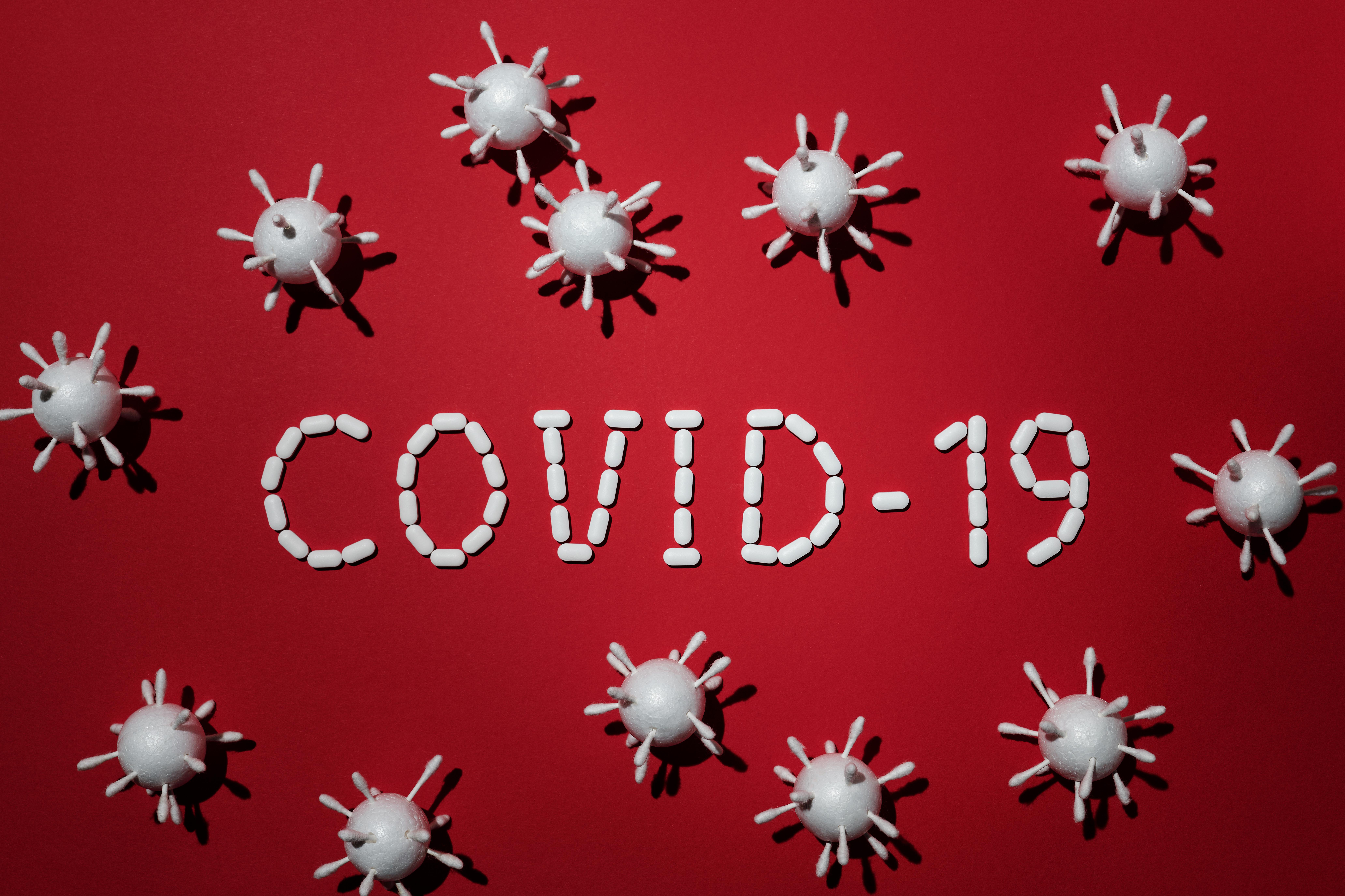 Schriftzug: Covid 19; aus weißen Tabletten auf rotem Hintergrund