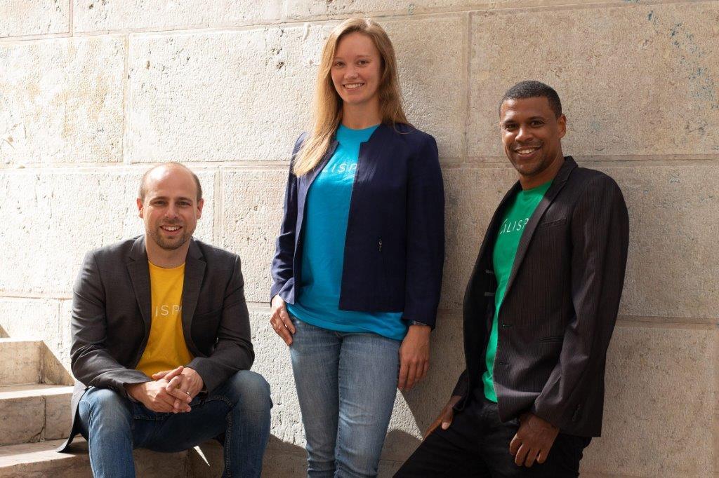 Zwei Männer und eine Frau; ein Mann sitzt auf einer Treppe, die anderen lehnen an einer Wand