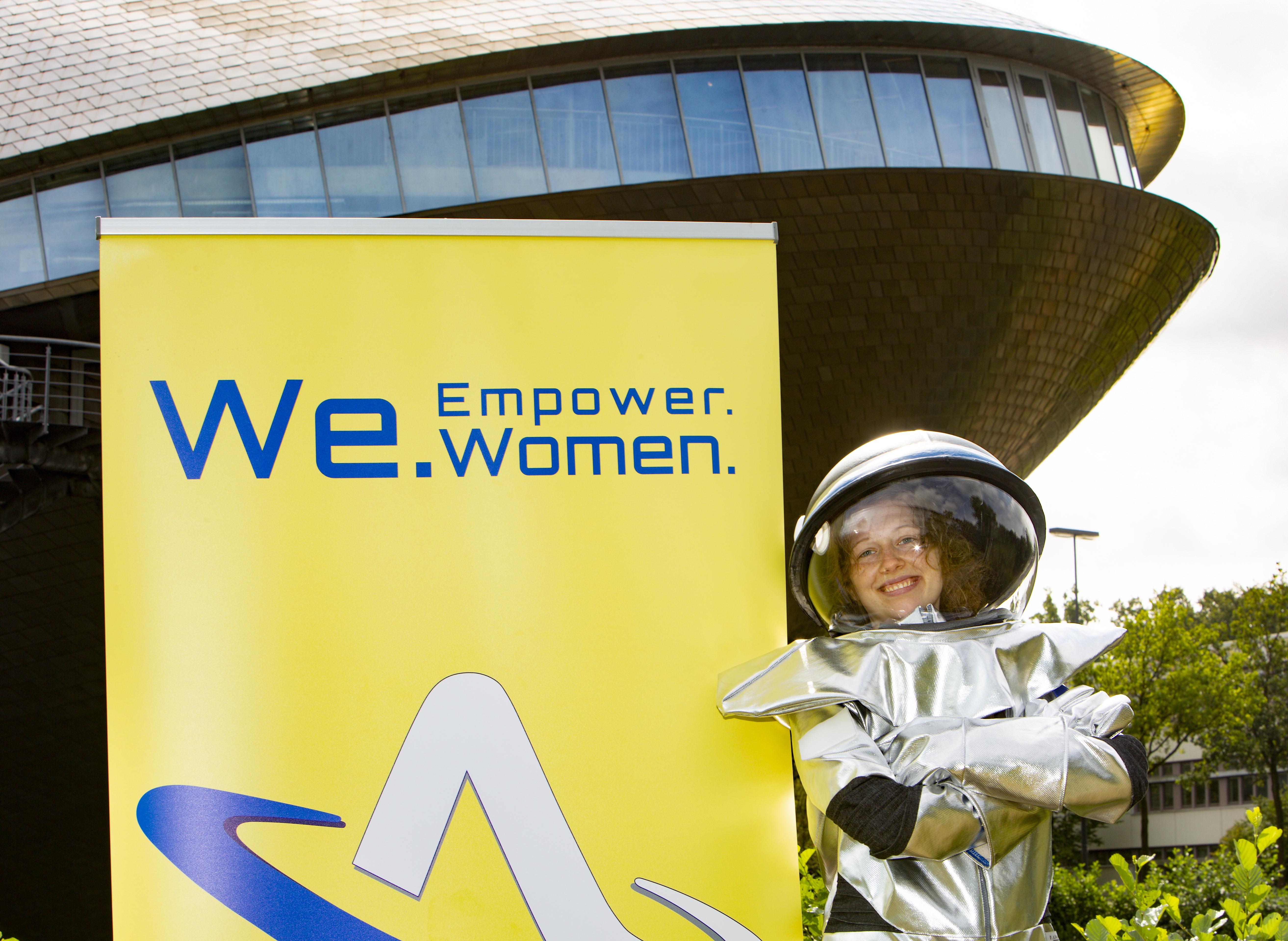 Eine Frau im Astronautinnenanzug, sowie ein Plakat zur We - Women Empower