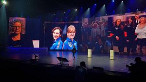 Eine Frau auf einer Bühne; hinter ihr werden Bilder von Astronautinnen präsentiert