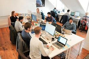 Einige Personen sitzen am Arbeitsplatz vor dem Laptop