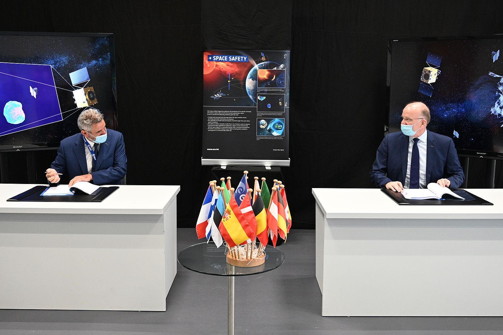 Zwei Männer unterzeichnen jeweils Verträge; im Hintergrund ein Plakat der Space Safety