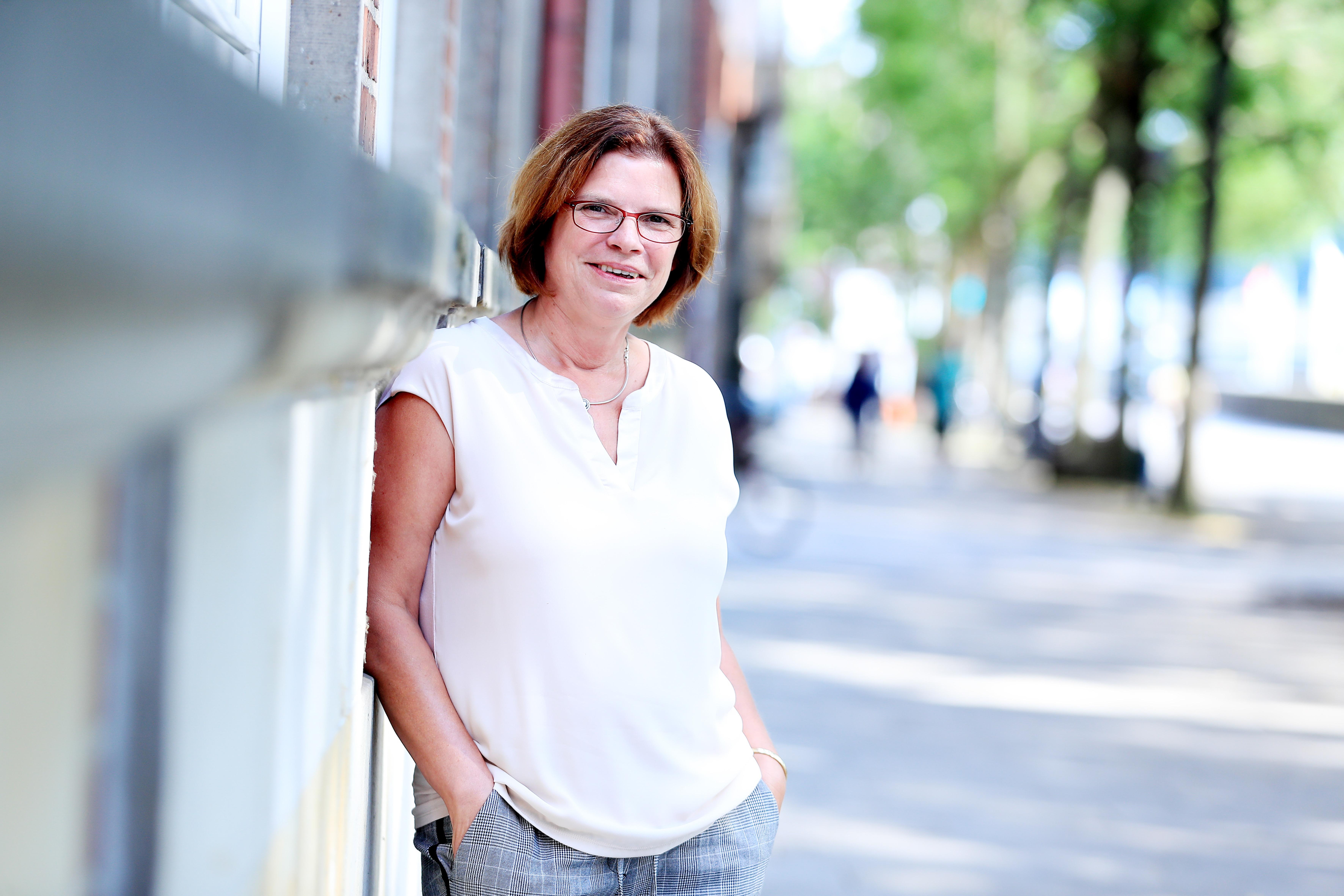 Kristina Vogt steht an ein Gebäude gelehnt
