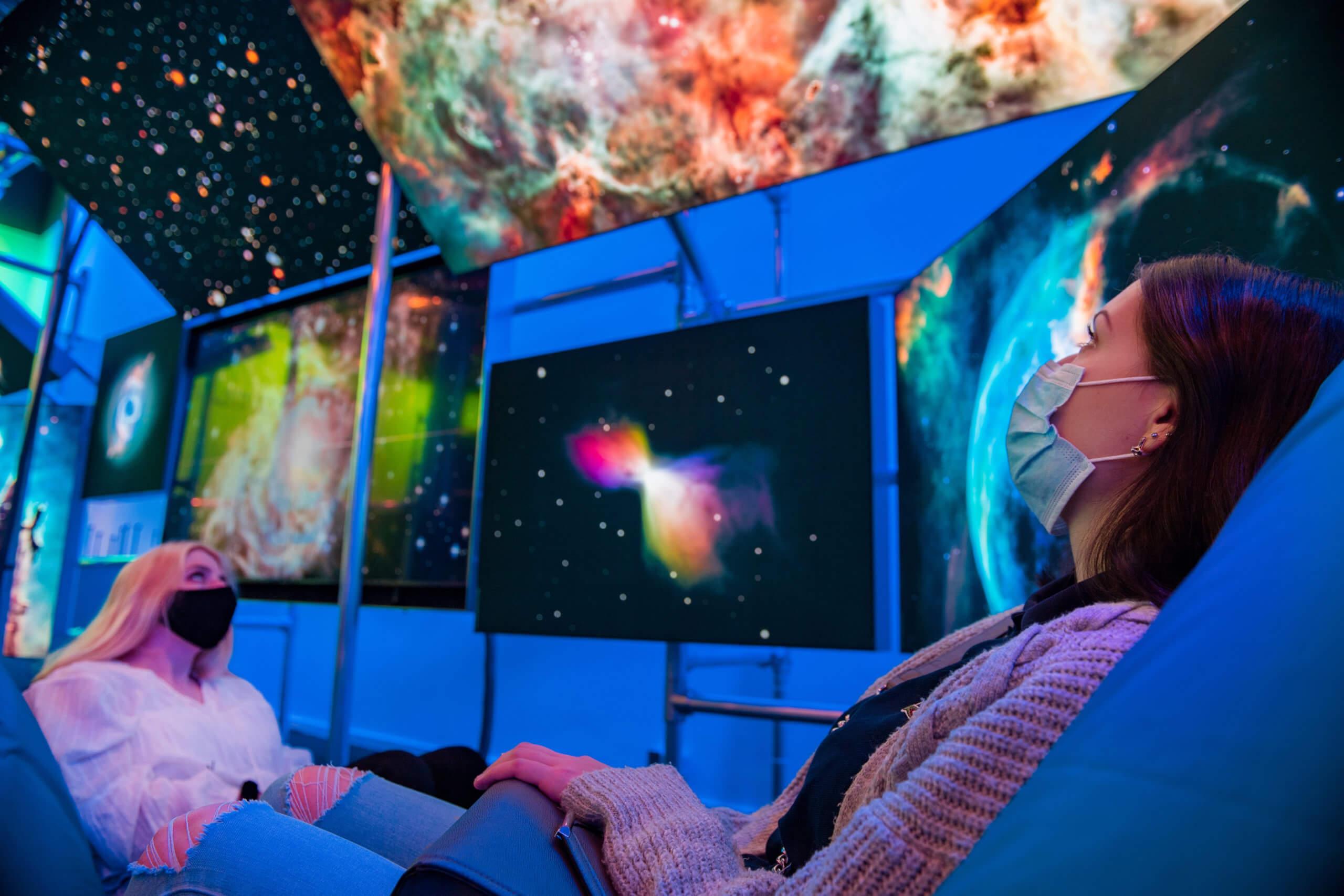 Zwei Frauen sitzen auf Sesseln und schauen kosmische Bilder an der Decke