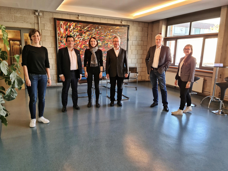 Sechs Personen stehen in einem Raum und lächeln in die Kamera