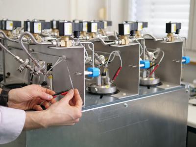 Zwei Hände, die an einem technischen Aufbau arbeiten