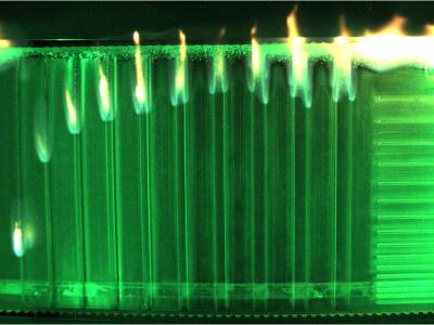 Brennende Plexiglasstäbe in grüner Flüssigkeit