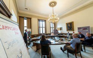 Einige Personen sitzen um einen Tisch und zwei Personen präsentieren ihre Ideen