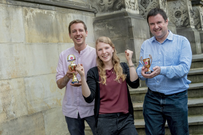 Drei Personen die einen Preis gewonnen haben und sich freuen
