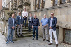 Sieben Jurymitglieder vor einem Gebäude