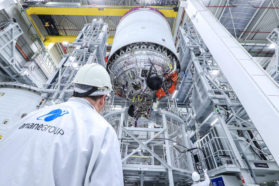 Eine Person schaut auf eine Raketenstufe im Werk