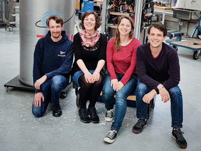 Vier junge Menschen sitzen auf einem Sockel und schauen in die Kamera